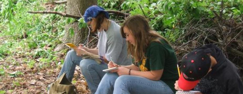 Students write in notebooks in forest woods.